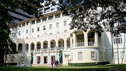 "Exterior of the Hawai'i State Art Museum building with ""No. 1 Capitol District"" across the top and 3 people along the walkway getting ready to enter the building."