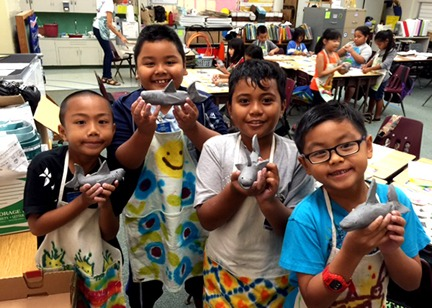 Four smiling students holding the clay shark sculptures made during an AITS residency program