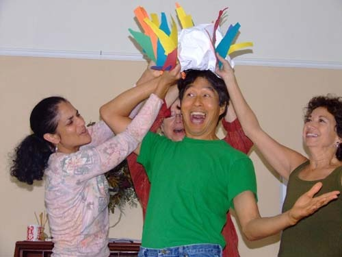 photo of 3 women holding a hat over a man's head