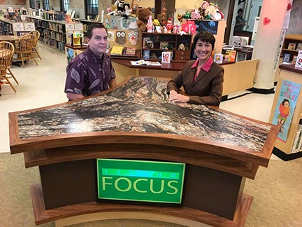 Jonathan Johnson and Lyla Berg seated behind a desk with the Island Focus logo
