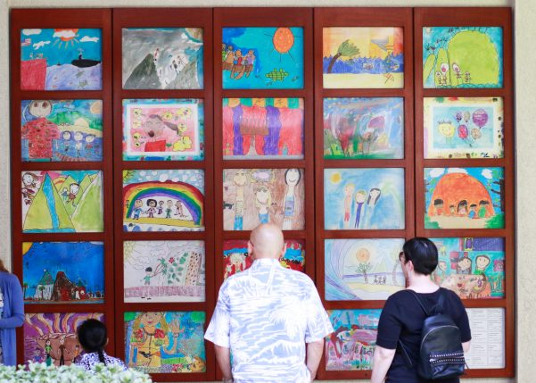 people looking at a display of student artwork