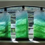 "Photograph of the sculpture ""Spirit of Manoa"" - 5 cast-glass structures in front of a window"