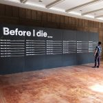 "Black wall stenciled with the words ""before I die..."""