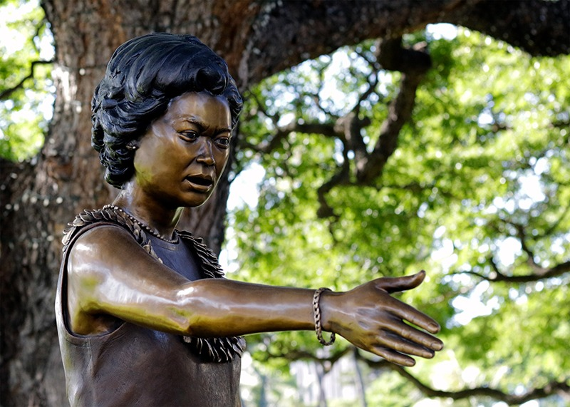 View of the bronze sculpture of Patsy T. Mink from the waist up, showing an outstretched arm.