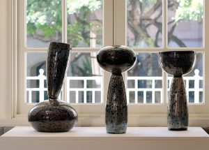 Three glass vessels in front of a window.