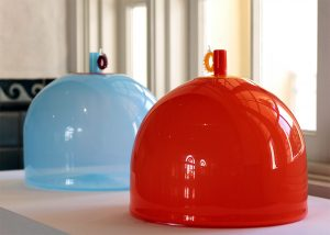Two glass vessels, one bright orange and one light blue.