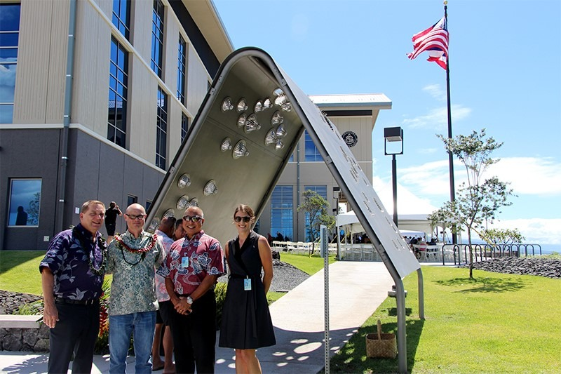"People standing in front of the ""Creating Kamaaina"" sculpture."