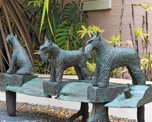 Sculpture of three dogs on a bench.