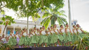 Group of young hula dancers walking onto a stage.