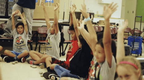 Children in a classroom raising their hands