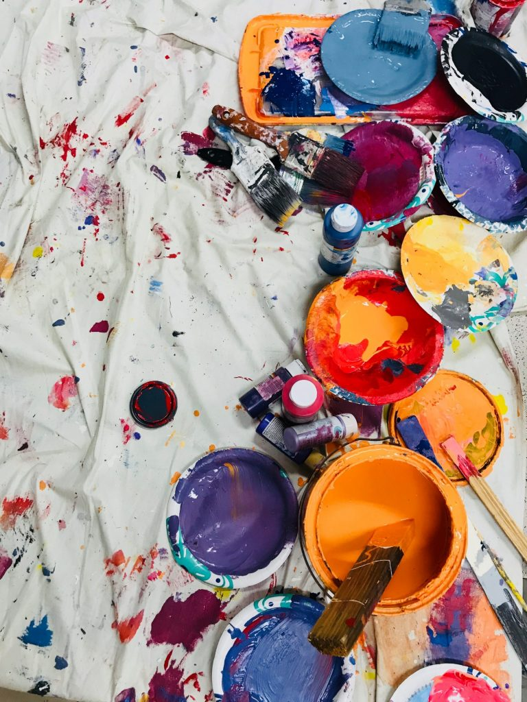 Paint containers and paint splattered across a canvas