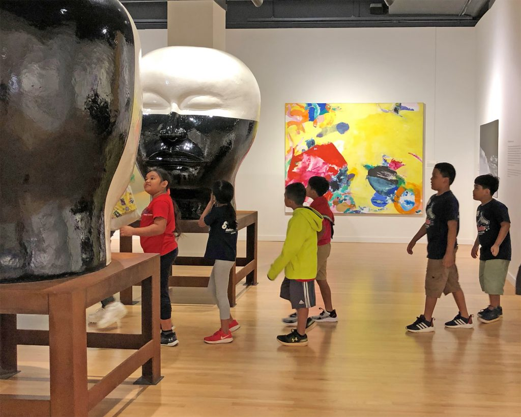 Students walking into a museum gallery.