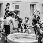 Black and white photograph of children playing around a small inflatable pool.