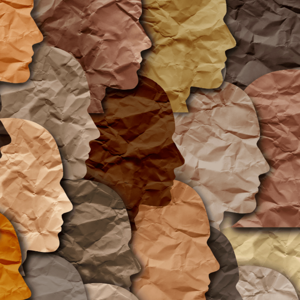 Silhouettes of human heads cut out of paper in various skin colors.