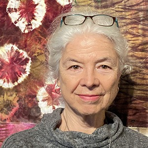 Ellen Crocker in front of a quilted wall hanging