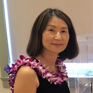 Hannah Shun. She is wearing a black shirt and a purple and white orchid lei.