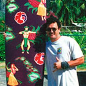 Jeff Pagay standing next to a colorful surfboard, making a shaka sign.