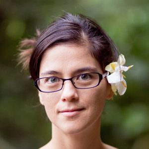 Laurel Nakanishi. Laurel is wearing glasses and there is a flower tucked behind one ear.