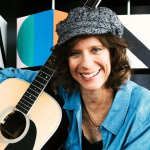 Priscilla Sanders holding a guitar
