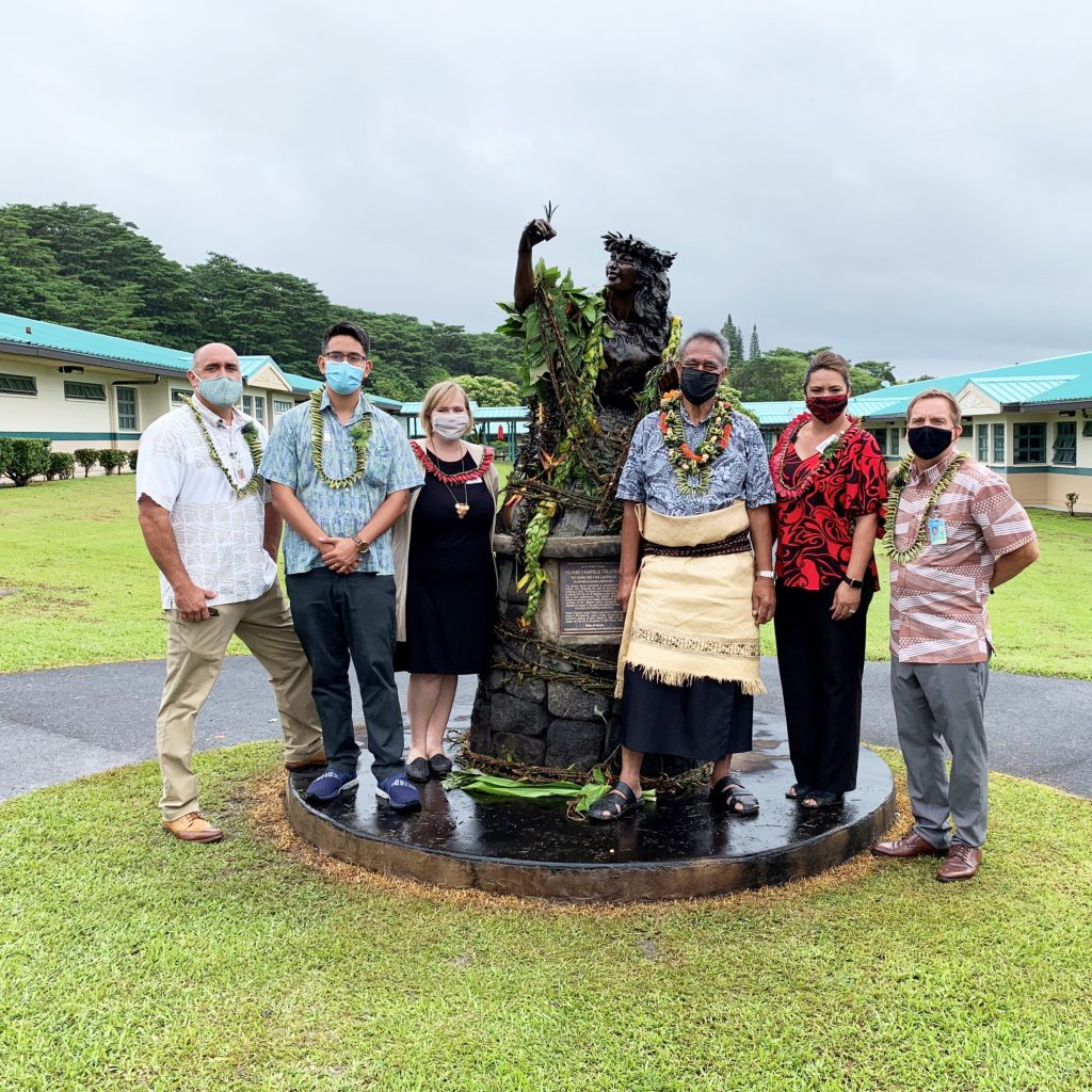 People standing next to a bronze statue. The statue is adorned with fresh lei.